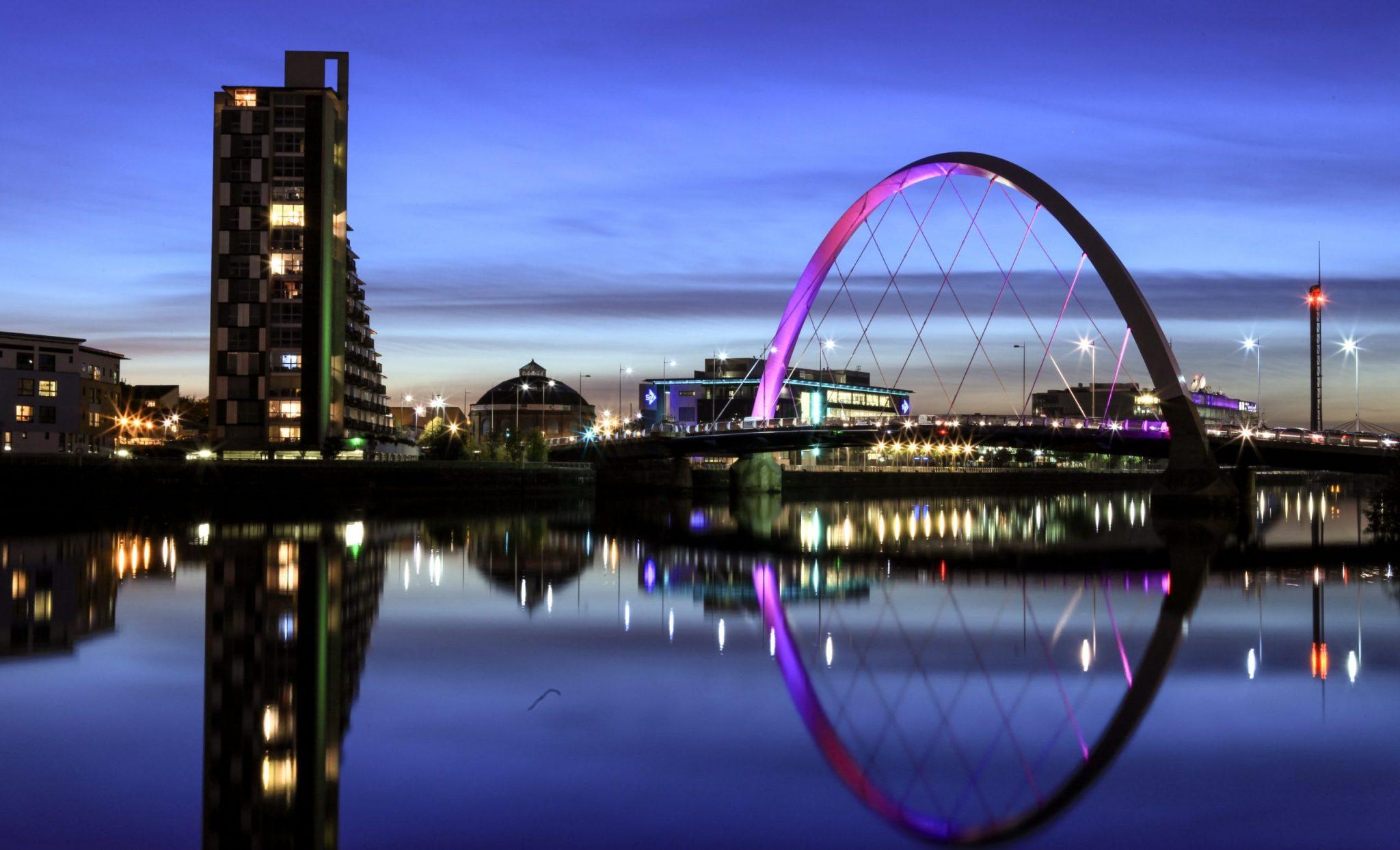 Glasgow arc bridge lit up purple at night time